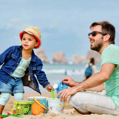 un père et son fils sur la plage entrain de jouer